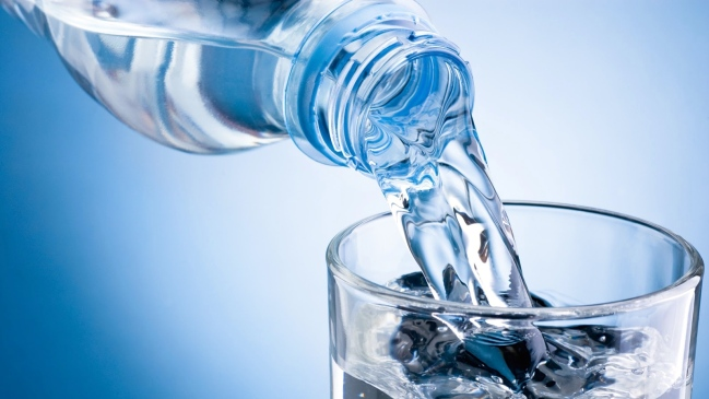 Pouring water from bottle into glass on blue background