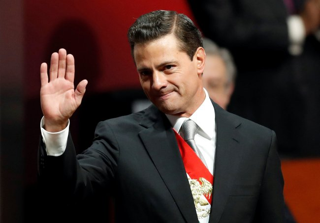 Mexico's President Enrique Pena Nieto waves as he arrives to deliver his sixth and last State of the Union address at the National Palace in Mexico City