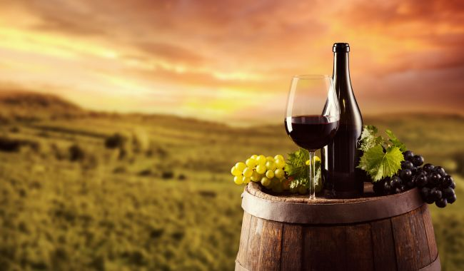 46471289 - red wine bottle and glass on wooden keg. vineyard on background